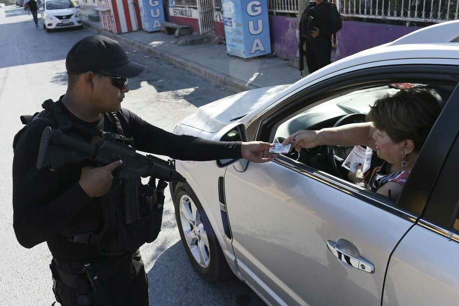 A Tamaulipas State Police officer checks vehicle documents at a checkpoint on Bulevar del Maestro in Reynosa, Mexico, Sunday, Nov. 5, 2017. Tamaulipas Gov. Francisco Cabeza de Vaca initiated the checkpoints in October as an effort to curb criminal groupÕs violence including carjackings. The police searches for stolen vehicles, drugs and guns. Photo: JERRY LARA / San Antonio Express-News / San Antonio Express-News