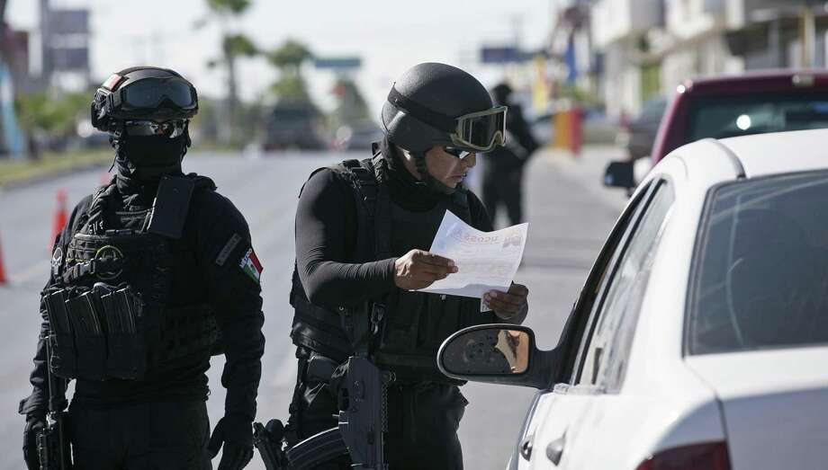 Tamaulipas State Police officers review paperwork on a vehicle at a checkpoint in Reynosa, Mexico, Sunday, Nov. 5, 2017. Tamaulipas Gov. Francisco Cabeza de Vaca initiated the checkpoints in October as an effort to curb criminal groupÕs violence including carjackings. The police searches for stolen vehicles, drugs and guns. Photo: JERRY LARA / San Antonio Express-News / San Antonio Express-News