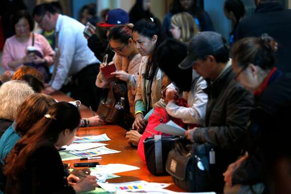 Applicants seeking U.S. citizenship (right) register for a Pathways to Citizenship workshop with volunteers at City College in San Francisco, Calif. on Saturday, Feb. 3, 2018.