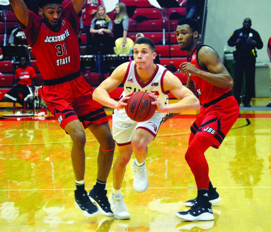SIUE point guard Christian Ellis, center, steps through a double team of Jacksonville State defenders to deliver a pass in the second half.