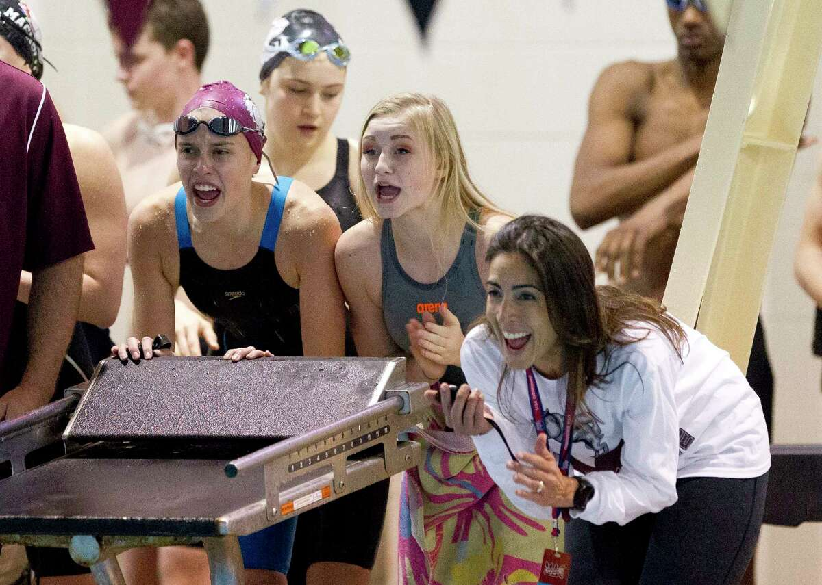 Magnolia swimmers cheer during the girls 200-yard medley relay during the Region VI-5A Swimming & Diving Championships at the Michael D. Holland Aquatic Center, Saturday, Feb. 3, 2018, in Magnolia.