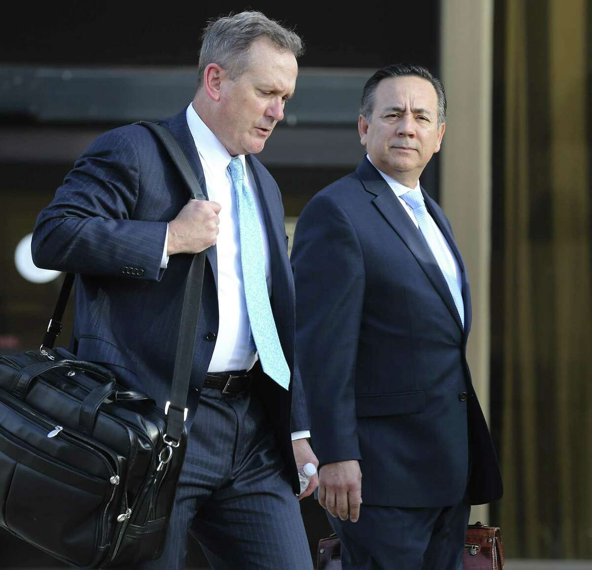 State Sen. Carlos Uresti (right) leaves with his attorneys from the John Wood Federal Courthouse after another day of testimony surrounding his indictment last year on 11 felony charges, including conspiracy to commit wire fraud, securities fraud and money laundering, in connection with his role at FourWinds Logistics. (Kin Man Hui/San Antonio Express-News)