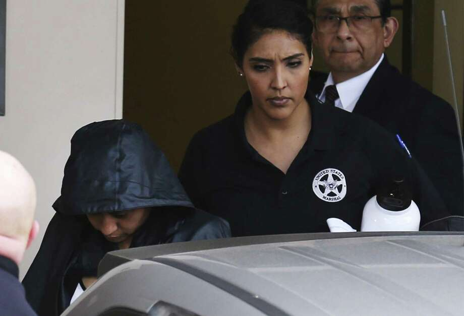 Hidden under security and a jacket, Denise Cantu (left), the Harlingen woman who prosecutors allege Carlos Uresti carried on a sexual relationship with and then exploited by convincing her to invest in a startup oil field company, has taken the witness stand in the state senator's criminal fraud trial on Thursday, Feb. 1, 2018. (Kin Man Hui/San Antonio Express-News) Photo: Kin Man Hui, Staff / San Antonio Express-News / ©2018 San Antonio Express-News