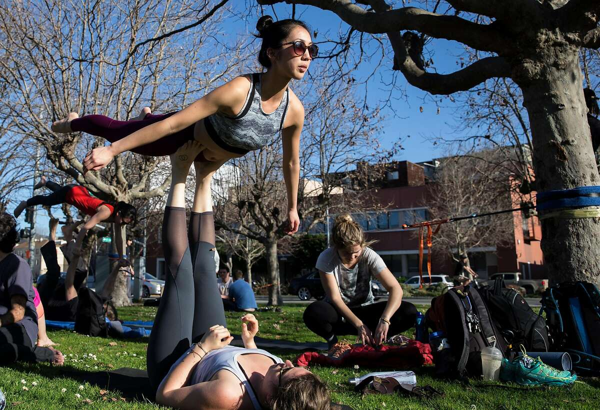Molly Pearson of Berkely uses her feet to support Christina Chen of Oakland while she balances at Lake Merritt Saturday, Feb. 3, 2018 in Oakland, Calif. Temperatures reaching into the mid to high 70s this weekend are expected to break records across the Bay Area for this time of the year.