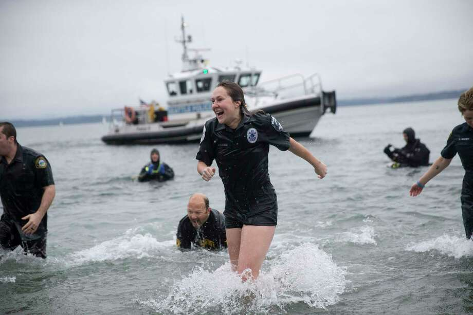 "The ""Blue Orphans"" police fundraising team reacts to the cold water during the Washington Special Olympic Polar Plunge at Golden Gardens on Saturday, Feb. 3, 2018. Photo: GRANT HINDSLEY, SEATTLEPI.COM / SEATTLEPI.COM"