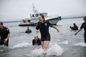 """The """"Blue Orphans"""" police fundraising team reacts to the cold water during the Washington Special Olympic Polar Plunge at Golden Gardens on Saturday, Feb. 3, 2018."""
