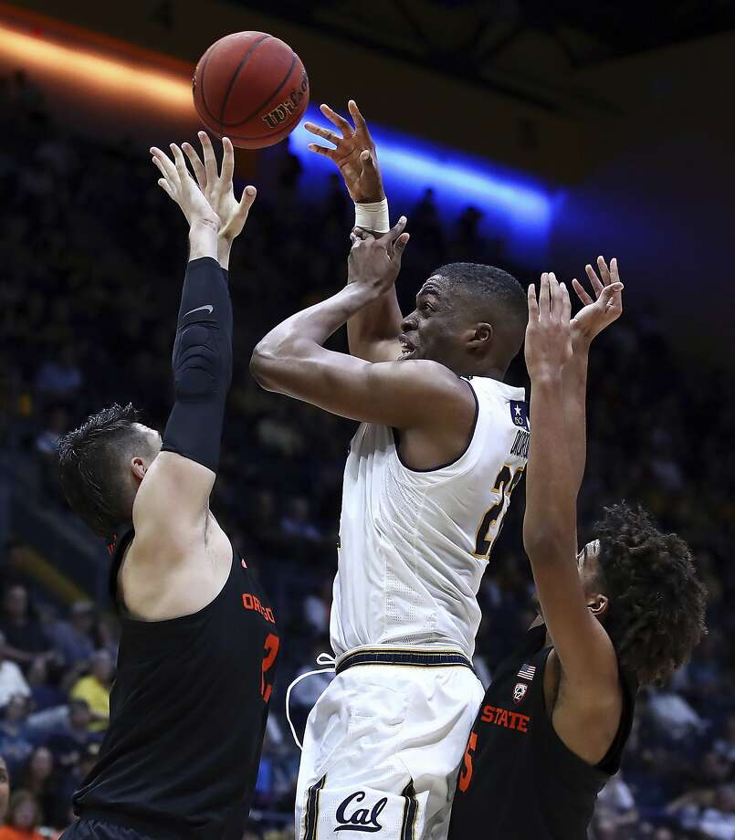 California's Kingsley Okoroh, center, passes the ball away from Oregon State's Gligorije Rakocevic, left, and Ethan Thompson in the first half of an NCAA college basketball game Saturday, Feb. 3, 2018, in Berkeley, Calif. (AP Photo/Ben Margot) Photo: Ben Margot, Associated Press