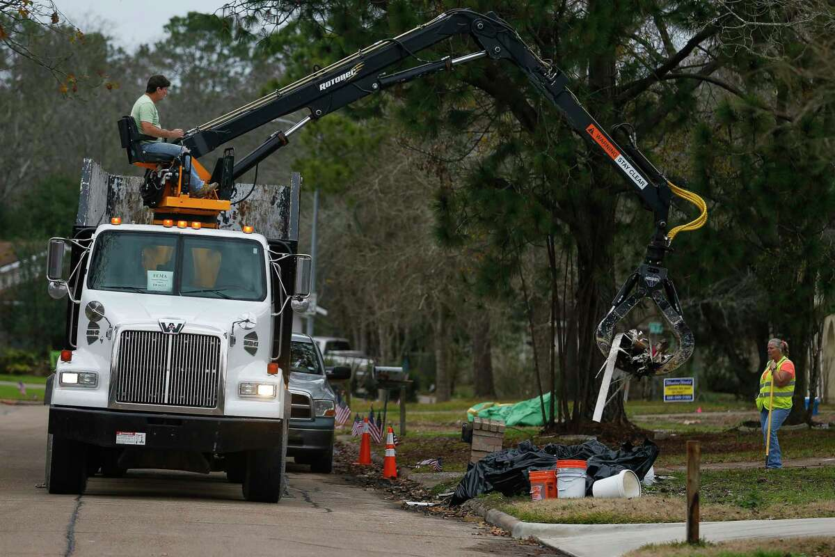 A FEMA disaster recovery vehicle picks up flood debris from a home in the Forest Bend neighborhood of Friendswood.