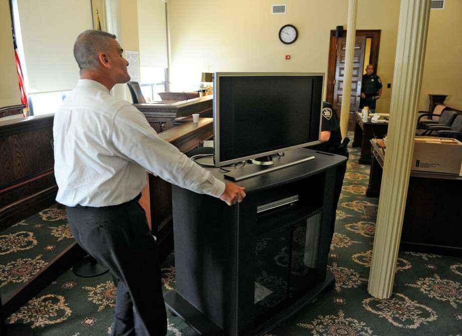 Chief Court Clerk Richard Riley moves a video screen into the courtroom of Judge Andrew Ceresia Wednesday in the Rensselaer County Courthuse in Troy  just before a suppression hearing. Murder defendant Adrian Thomas is trying to get a nine-hour video of his interrogation by police thrown out as evidence. (Skip Dickstein / Times Union) Photo: Skip Dickstein