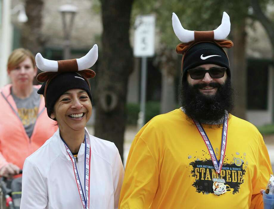Sandra Surprise (left) and her husband, Jason, wear horns after running in the 5K Stampede preceding the annual Western Heritage parade and cattle drive on Saturday, Feb. 3, 2018. Herds of onlookers along Houston and Alamo Streets lined the sidewalks as Longhorns moseyed along downtown and past the Alamo on Saturday, Feb. 3, 2018. The route took the horned beasts past the Shrine of Texas and concluded at La Villita as a crowd gathered around the holding pen to get a closer glimpse of the official state mammal (large) of Texas. Young and old alike were fascinated to see the Longhorns casually cruise past RiverCenter Mall with sale signs posted in the window. As the last long-horned Longhorn climbed into an awaiting trailer, people made a point to take one last selfie to mark the event which is the kickoff of the 2018 San Antonio Stockshow and Rodeo which starts next Thursday. Photo: Kin Man Hui, San Antonio Express-News / ©2018 San Antonio Express-News
