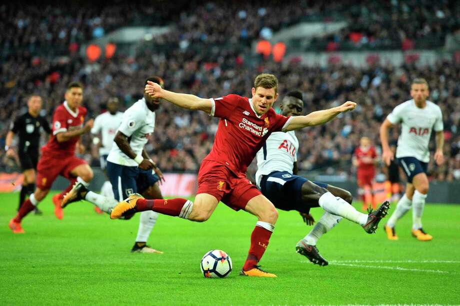 Liverpool's English midfielder James Milner (C) vies with Tottenham Hotspur's Colombian defender Davinson Sanchez during the English Premier League football match between Tottenham Hotspur and Liverpool at Wembley Stadium in London, on October 22, 2017. / AFP PHOTO / Glyn KIRK / RESTRICTED TO EDITORIAL USE. No use with unauthorized audio, video, data, fixture lists, club/league logos or 'live' services. Online in-match use limited to 75 images, no video emulation. No use in betting, games or single club/league/player publications.  / GLYN KIRK/AFP/Getty Images Photo: GLYN KIRK / AFP or licensors