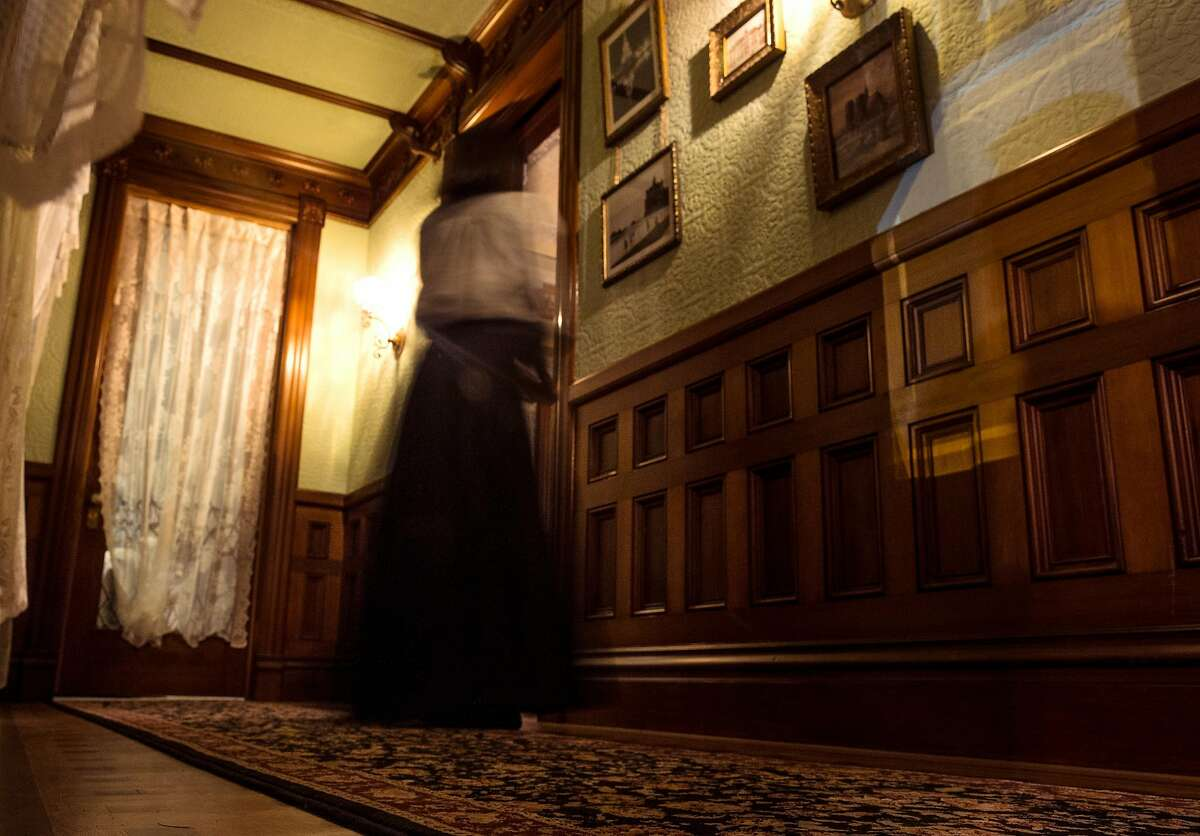 """A woman walks down one of the many hallways of the Winchester Mystery House during an event celebrating the opening night of the Hollywood film """"Winchester"""" at the Winchester Mystery House Friday, Feb. 2, 2018 in San Jose, Calif."""