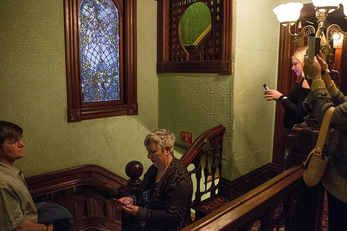 """Guests take photos of the most expensive window in the Winchester Mystery House, purchased in its day by Sarah Winchester at $1500, during an event celebrating the opening night of the Hollywood film """"Winchester"""" at the Winchester Mystery House Friday, Feb. 2, 2018 in San Jose, Calif."""