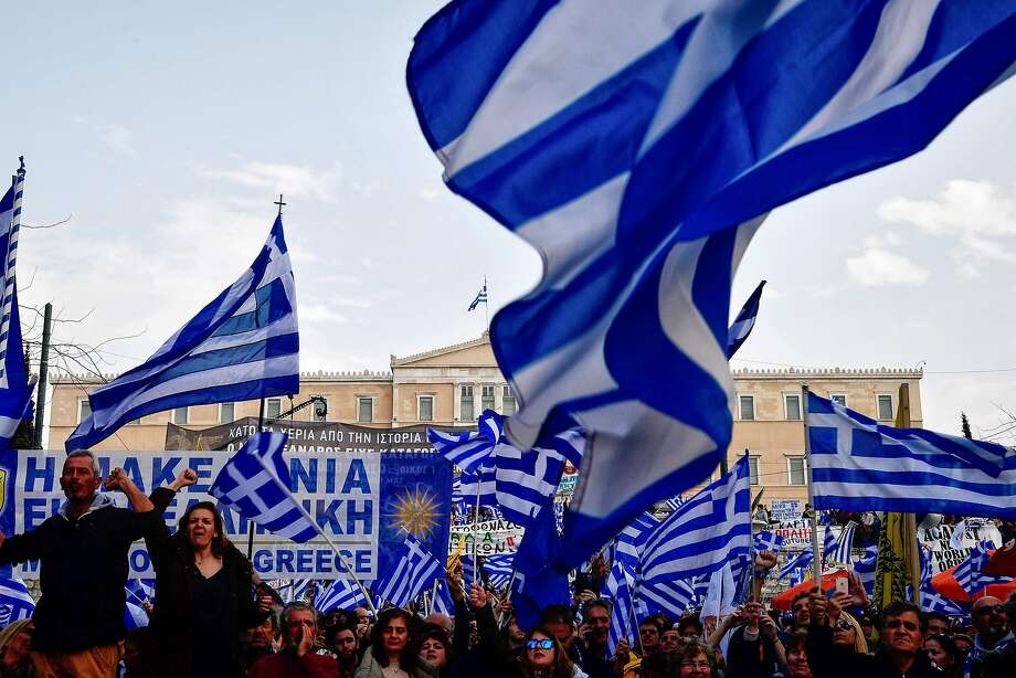 TOPSHOT - People wave flags of Greece as they demonstrate to urge the government not to compromise in the festering name row with neighbouring Macedonia, in front of the parliament of Greece, located in the Old Royal Palace (background), at the Syntagma Square in Athens, on February 4, 2018. / AFP PHOTO / LOUISA GOULIAMAKILOUISA GOULIAMAKI/AFP/Getty Images Photo: LOUISA GOULIAMAKI, AFP/Getty Images