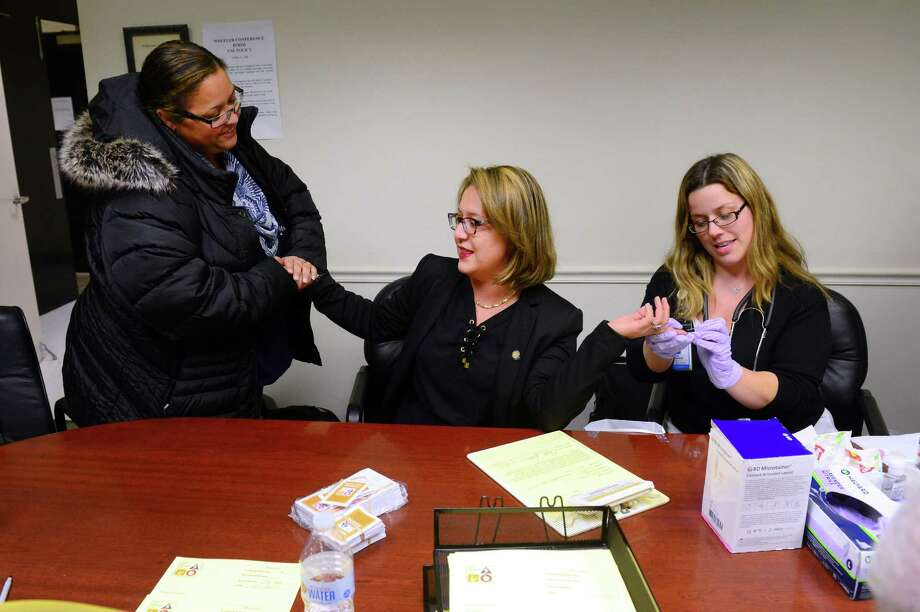 Bridgeport City Councilwoman Milta Feliciano, center, is comforted by city employee Albertina Baptista, left, as Nicole Rogucki, R.N. takes a sample of blood during the Know Your Numbers health screening event at City in Bridgeport, Conn., on Tueday Jan. 17, 2017. The Bridgeport Department of Health and Social Services will co-host a screening 5:30 to 7:30 p.m. on Monday, Feb. 5, 2018, before the regularly scheduled Bridgeport City Council meeting at Bridgeport City Hall, 45 Lyon Terrace, as part of this year's Know Your Numbers campaign for heart month, which is February. Photo: Christian Abraham / Christian Abraham / Connecticut Post