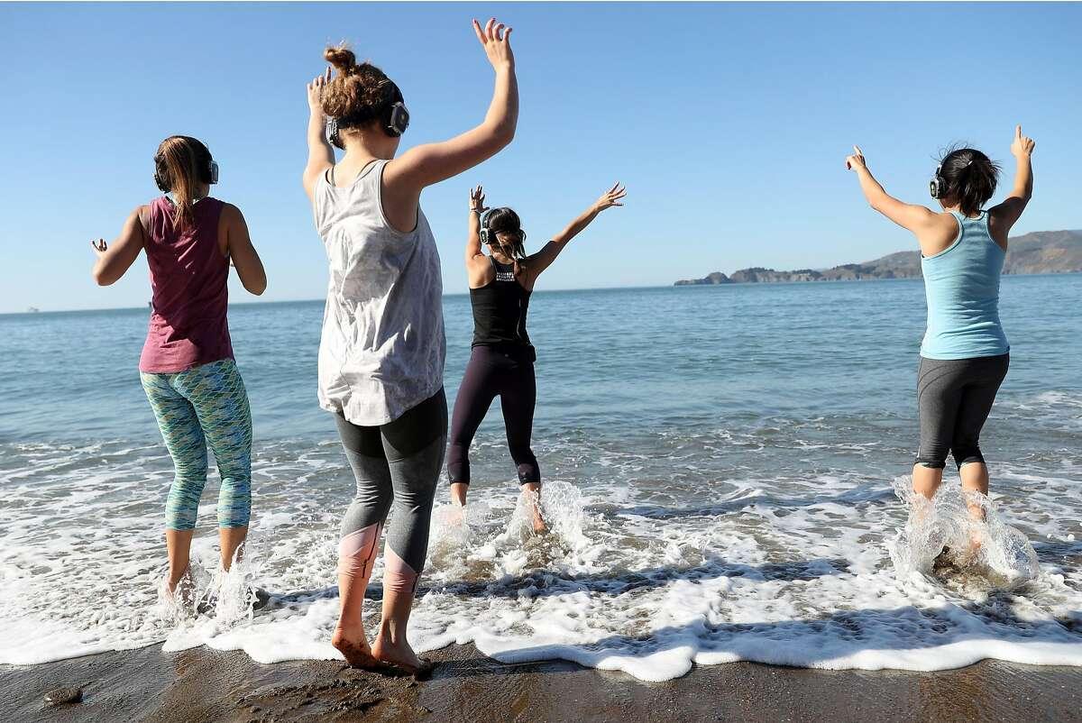 Julie Aiello (center) leads an Outdoor Yoga SF class on Baker Beach in San Francisco, Calif., on Sunday, February 4, 2018.