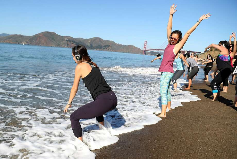 Julie Aiello (center) leads an outdoor yoga class on Baker Beach in San Francisco Sunday Photo: Scott Strazzante, The Chronicle