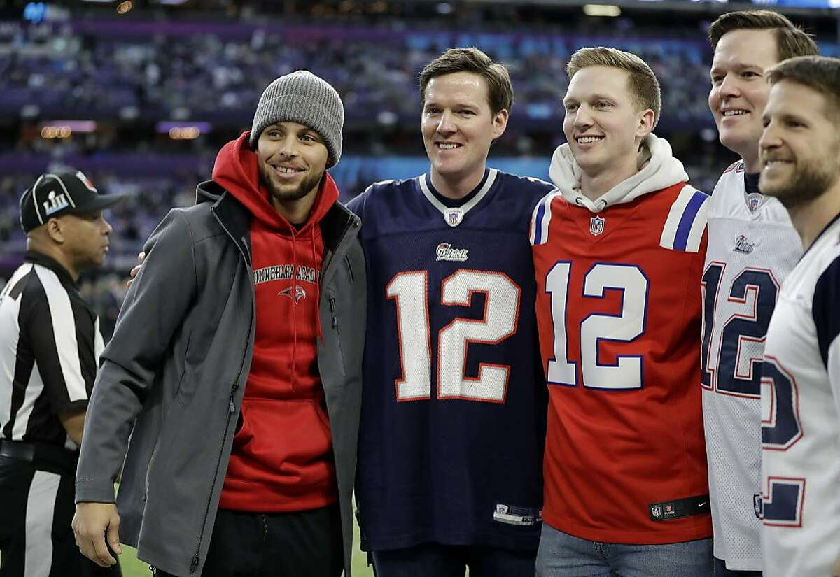 Golden State Warriors basketball player Stephen Curry, left, poses with New England Patriots fans before the NFL Super Bowl 52 football game between the Philadelphia Eagles and the Patriots Sunday, Feb. 4, 2018, in Minneapolis.