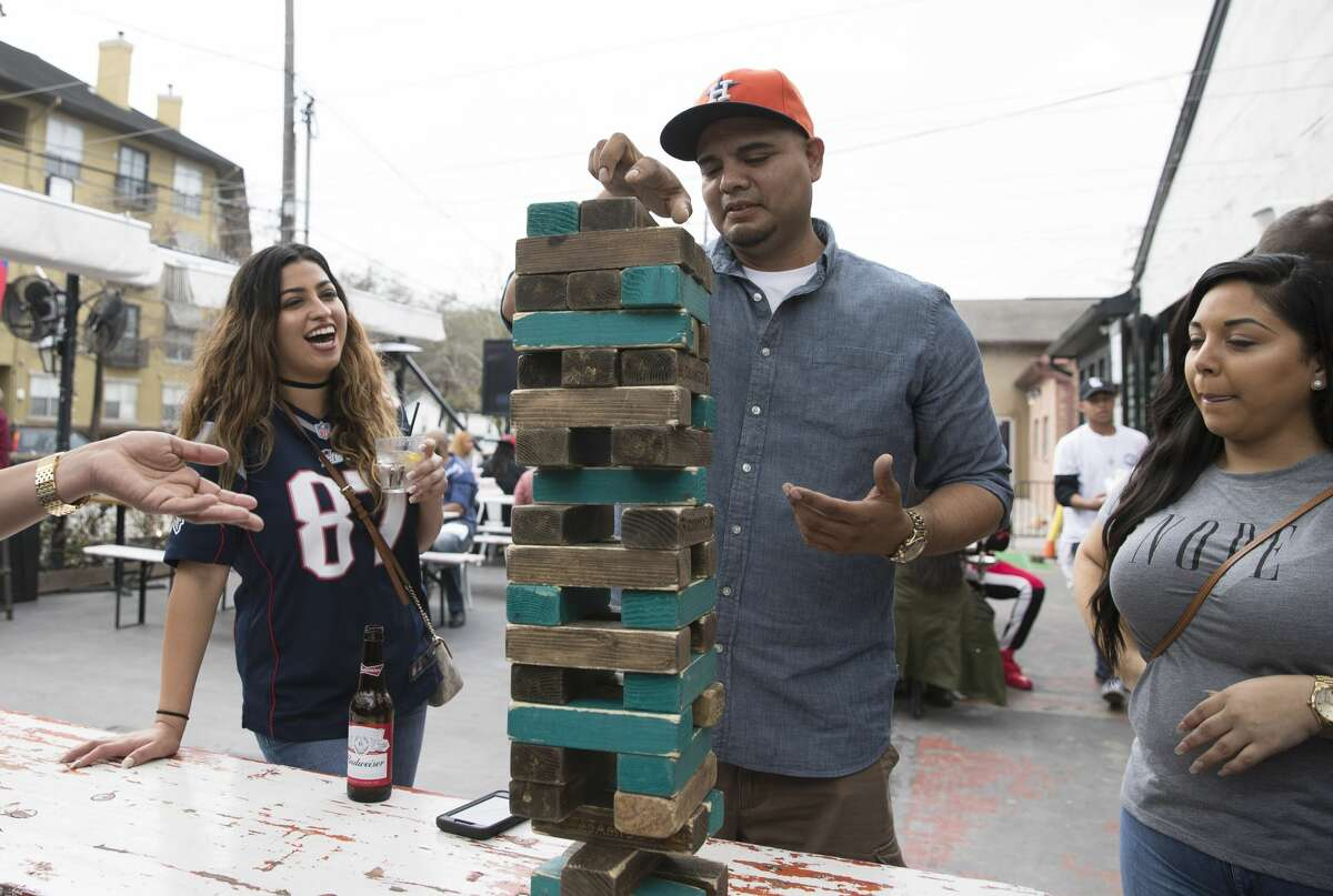Robert DeLeon, center, and Jessie Mejia, who is sporting a New England Patriots jersey, play Jenga with a group of friends at Belle Station before the Super Bowl LII on Sunday, Feb. 4, 2018, in Houston. ( Yi-Chin Lee / Houston Chronicle )