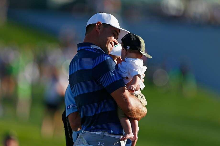 Gary Woodland holds his son, Jaxson Lynn, after winning the Phoenix Open at TPC Scottsdale. Photo: Matt Sullivan, Getty Images