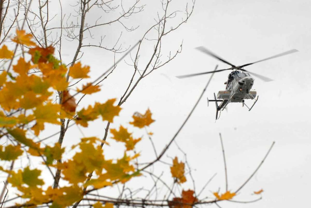 A State Police helicopter searches over the Hudson River in Watervliet Friday morning (Michael P. Farrell / Times Union)