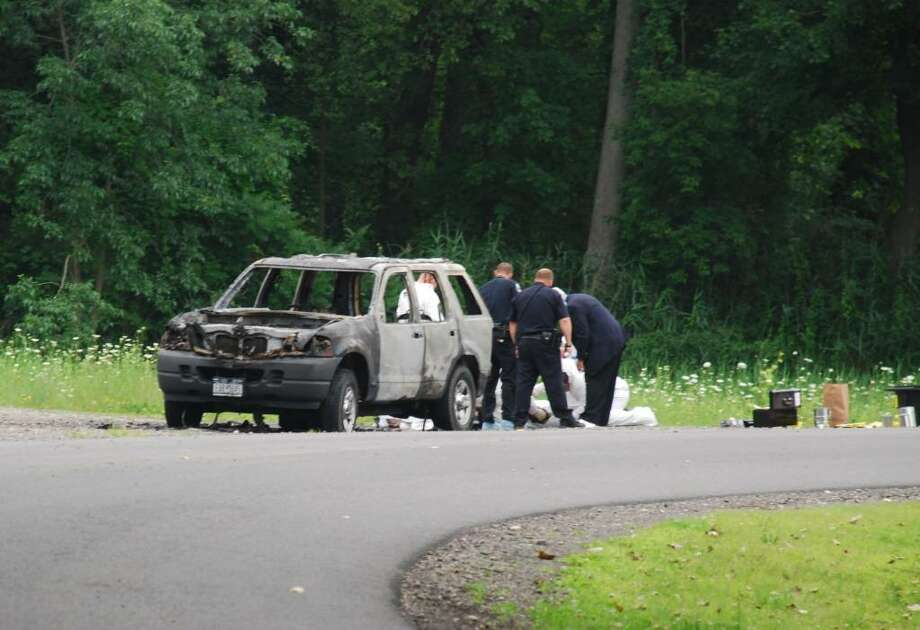 Officials investigate the scene of a fatal car fire on Lyons Road in Bethlehem. (Tom Hefferan Sr. / Special to the Times Union)