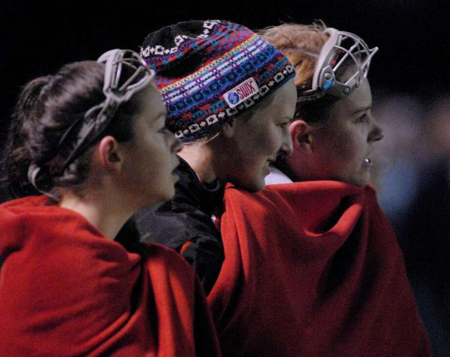 Niskayuna players Sydney Bowker, left, Erin Down, center, and Katherine Pearse try to stay warm  while watching teammates play Saratoga in the Class A field hockey Title game at Shenendehowa. (Hans Pennink/Special to the Times Union) Photo: Hans Pennink