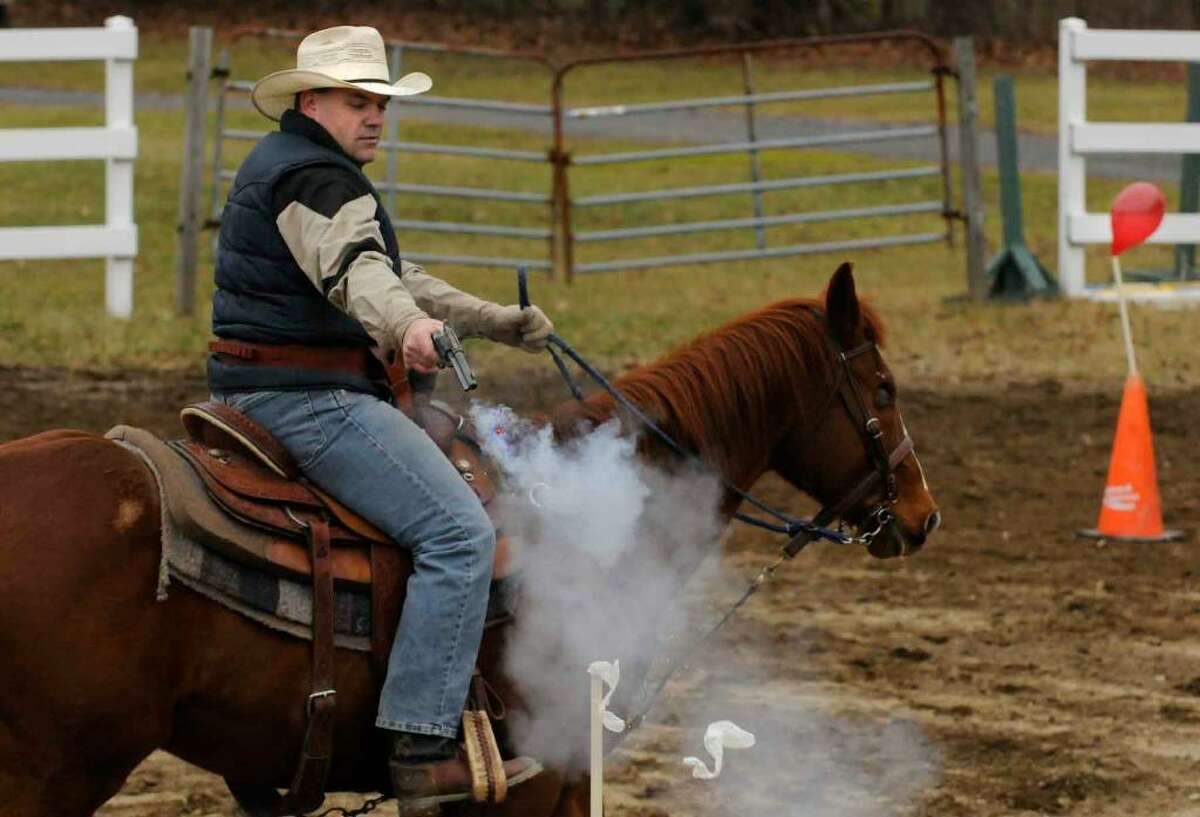 Scott Keyes of Greenwich, riding his horse, One Eyed Jack, shoots and bursts a balloon during a cowboy mounted shooting clinic at the 4-H Training Center in Milton. (Michael P. Farrell / Times Union)