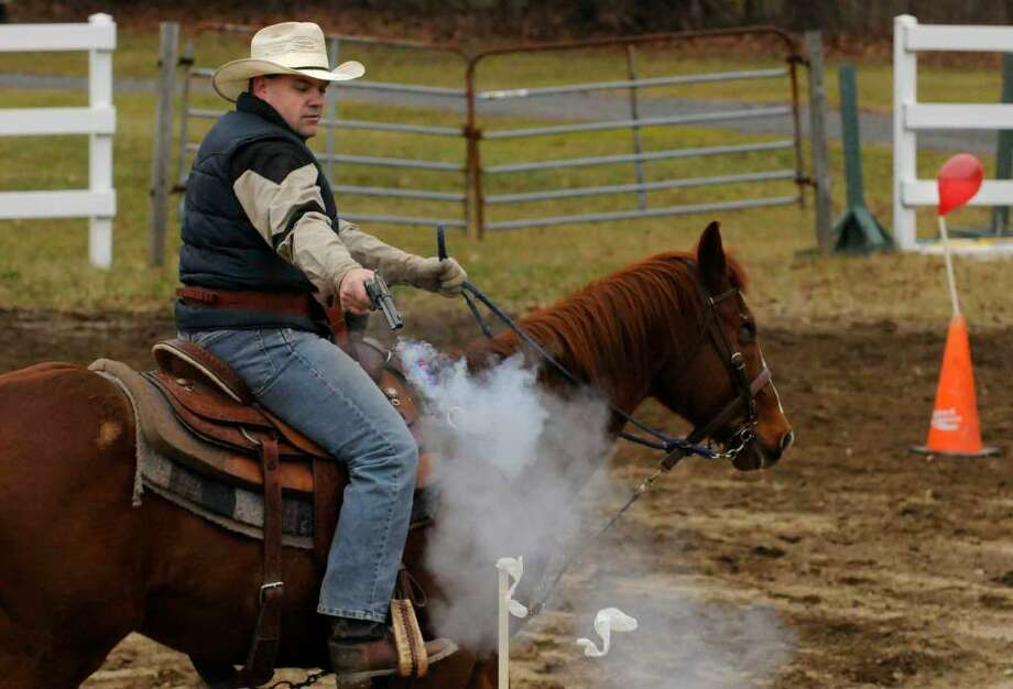 Scott Keyes of Greenwich, riding his horse, One Eyed Jack, shoots and bursts a balloon during a cowboy mounted shooting clinic at the 4-H  Training Center in Milton. (Michael P. Farrell / Times Union) Photo: MICHAEL P. FARRELL
