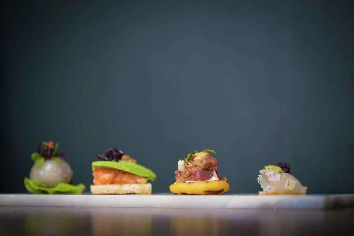 (Left to right) Tapioca Dumpling dish from Aqui is made out ground pork, peanut and salted radish. Cured Ikura made out of fermented salmon roe and avocado. Tuna Arepa made out of corn cake, radish and fish sauce. Madai made out of Japanese seabream, namchim, ponzu, shiso, daikon, wasabi and A5 fat. Thursday, Jan. 25, 2018, in Houston.