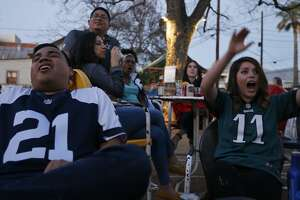 Football fans Angel Martinez (left) and Abigail Rodriguez react to an Eagles touchdown against the Patriots while watching Super Bowl LII Sunday Feb. 4, 2018 at The Friendly Spot.
