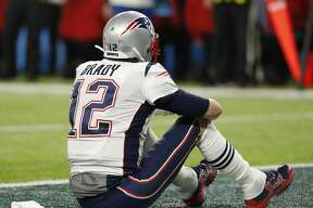 New England Patriots' Tom Brady sits on the field after the NFL Super Bowl 52 football game against the Philadelphia Eagles Sunday, Feb. 4, 2018, in Minneapolis. The Eagles won 41-33. (AP Photo/Charlie Neibergall)