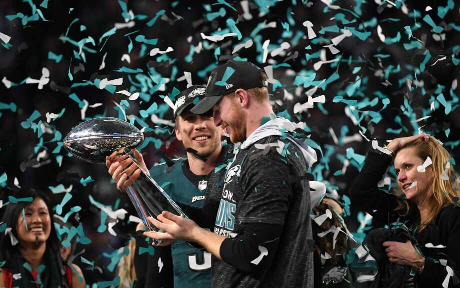 Quarterbacks Nick Foles (L) and Carson Wentz (R) of the Philadelphia Eagles celebrates following victory over the New England Patriots in  Super Bowl LII at US Bank Stadium in Minneapolis, Minnesota, on February 4, 2018. The Philadelphia Eagles scored a stunning 41-33 upset victory over the New England Patriots to win their first ever Super Bowl after a costly Tom Brady fumble ended the quarterback's tilt at history. Foles was a back-up who was thrust into the starting position when Carson Wentz suffered a season-ending injury in December.  / AFP PHOTO / TIMOTHY A. CLARYTIMOTHY A. CLARY/AFP/Getty Images Photo: TIMOTHY A. CLARY/AFP/Getty Images