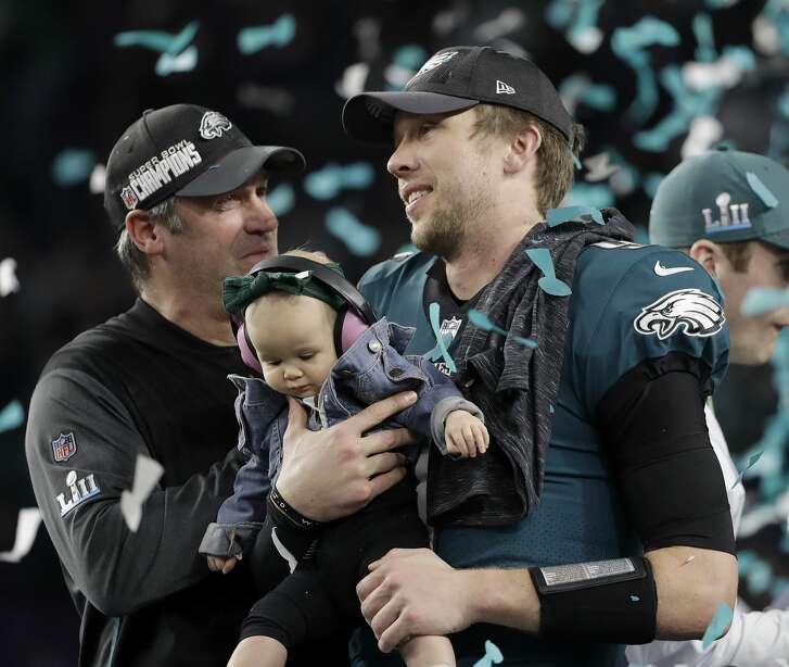 Philadelphia Eagles' Nick Foles, right, holds up his daughter Lily as and head coach Doug Pederson celebrate after the NFL Super Bowl 52 football game against the New England Patriots Sunday, Feb. 4, 2018, in Minneapolis. The Eagles won 41-33. (AP Photo/Chris O'Meara)