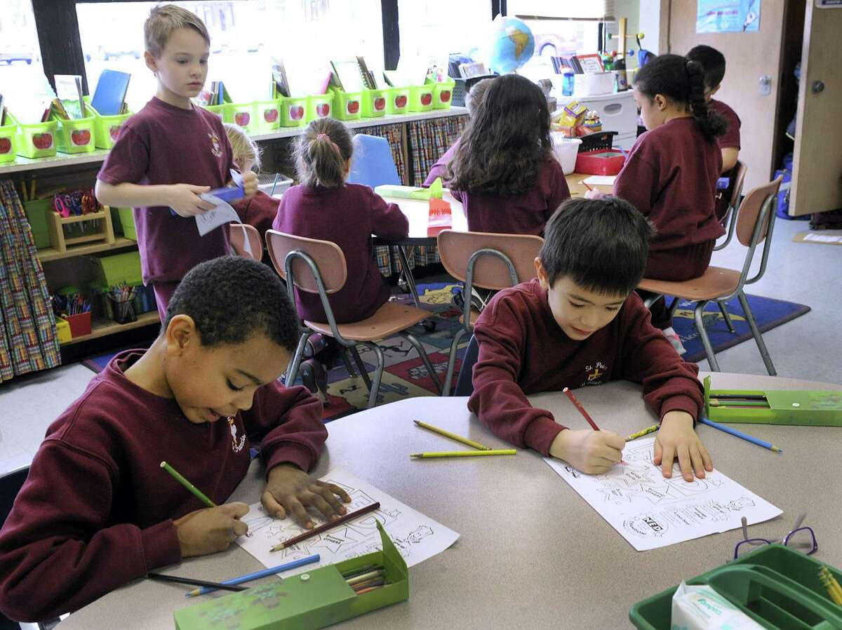 """Ian Bennett, left, and Anthony Bartek, both 8, and in the second grade, work on Math in a class that combines First and Second-graders at St. Peter/ St. Francis School in Torrington. The school is a """"multi-age"""" school where students are grouped by ability and taught individually. Bishop Frank J. Caggiano is hoping to use that same model at St. Joseph's School in Brookfield."""