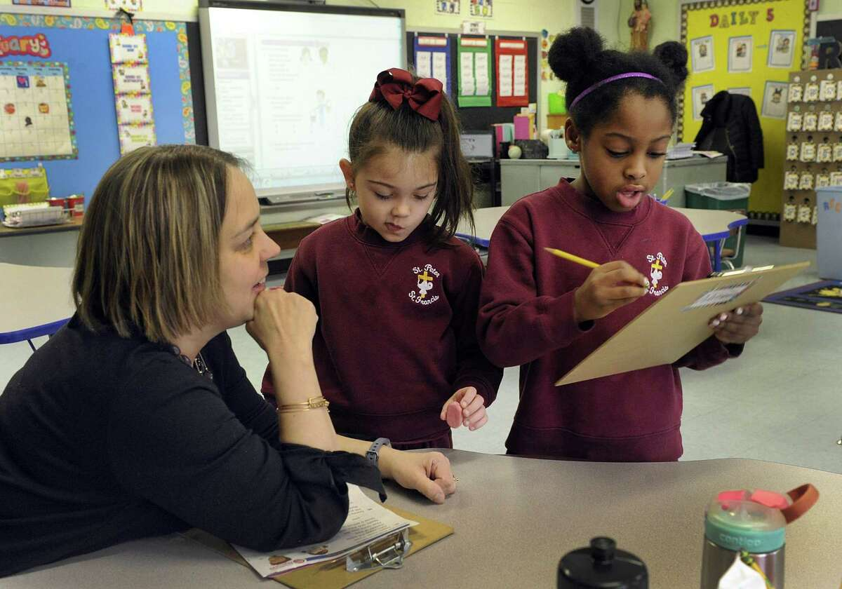 """Cathie Mastrogiovanni talks with Adrianna Lafleur, right, and Sophia Pellegren during a math session Thursday. Mastrogiovanni was teaching a class that combined first- and second-graders at St. Peter/St. Francis School in Torrington. This is a """"multi-age"""" school where students are grouped by ability and taught individually. Bishop Frank J. Caggiano, who leads the Bridgeport Diocese, hopes to use that same model at St. Joseph School in Brookfield."""
