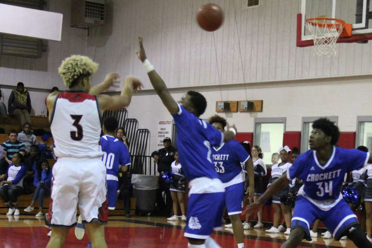 Trojan Jacoby Bishop (3) makes a shot over the heads of the defending Bulldogs.
