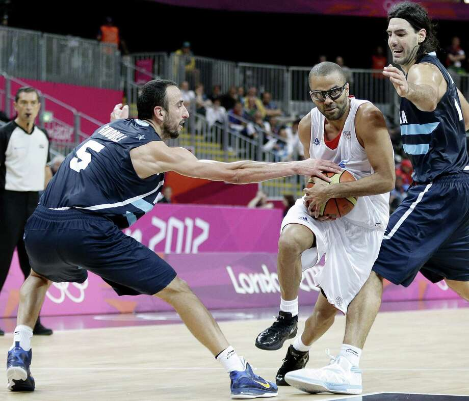 France's Tony Parker, center, drives between Argentina's Manu Ginobili (5) and Argentina's Luis Scola, right, during the second half of a preliminary men's basketball game at the 2012 Summer Olympics, Tuesday, July 31, 2012, in London. (AP Photo/Eric Gay) Photo: Eric Gay, STF / AP / AP