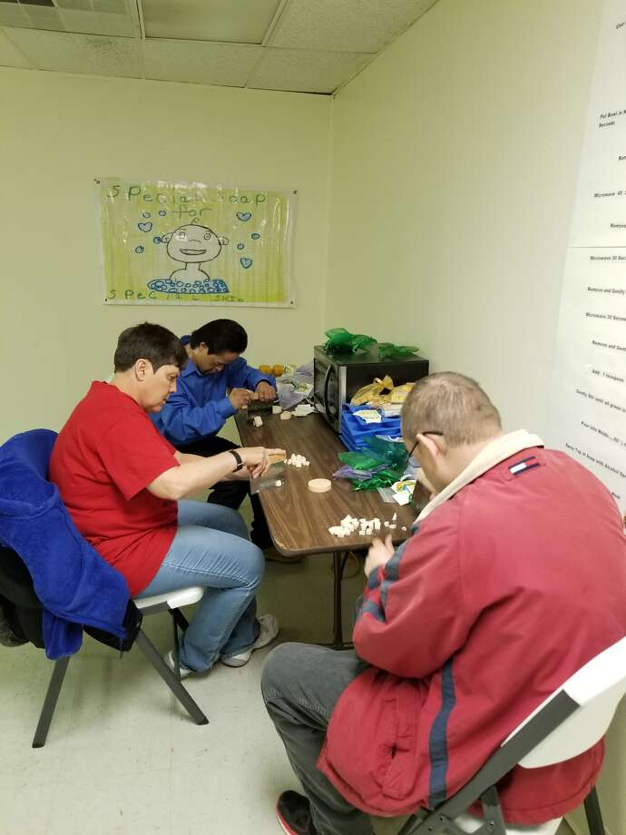 Client workers, Kelly Helms, left, Ramon Quintanilla and Jason Reed are busy making products for the big Valentine's sale at Diamond Suds, located at Central Plains Center's Tommy Lewis Industries in Plainview. Photo: Courtesy Photo