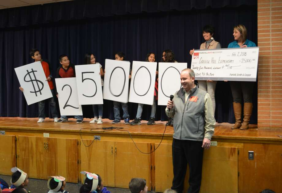 Parkhill, Smith & Cooper Director of Civil Engineering John Hamilton (standing front) speaks to students at College Hill Elementary Friday afternoon as PSC presents a check for $25,000, which includes $20,000 cash and $5,000 in pro-bono engineering fees. College Hill Students are standing on a stage behind him holding signs displaying the check amount while College Hill Elementary School Principal Lori Glenn and PSC employee Kristi Laverty hold the display check. Photo: William Carroll, Plainview Herald