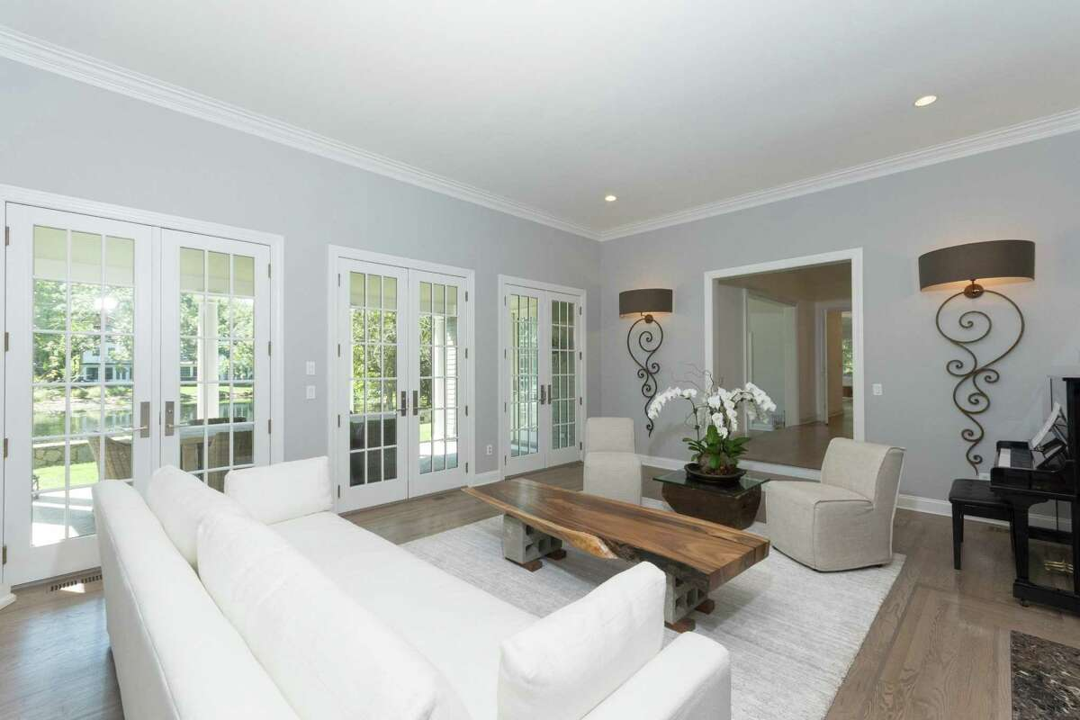 The formal living room has a marble fireplace and three sets of French doors to a long covered bluestone patio looking over the pond.