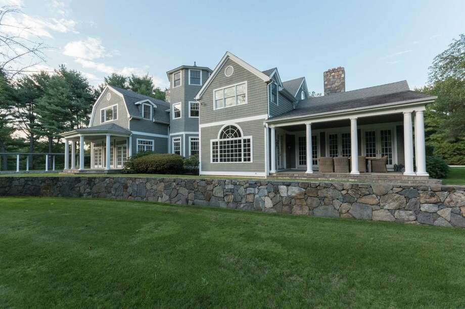 The 7,339-square-foot house in Westport, Conn. has several covered porches and patios. The custom-built shingle and stone colonial 