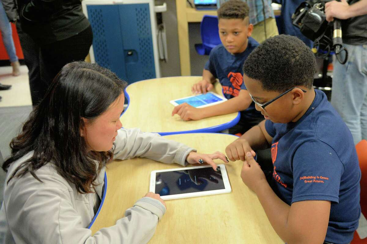 Ann Woo, Sr. Director of Corporate Citizenship at Samsung Electronics America helps a child with a tablet during the unveiling of an updated Tech Center at the Boys and Girls Club in Stafford, TX on Friday, February 2, 2018.