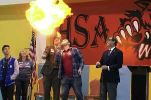 Mehmet Gokcek, a curriculum specialist at Harmony School of Innovation, involves featured guests in science experiments at the beginning of the Jan. 27 STEM Festival and open house. Gokcek gave a fire-breathing demonstration that he explained relies on basic principles of combustion of carbohydrates and involved cornstarch.