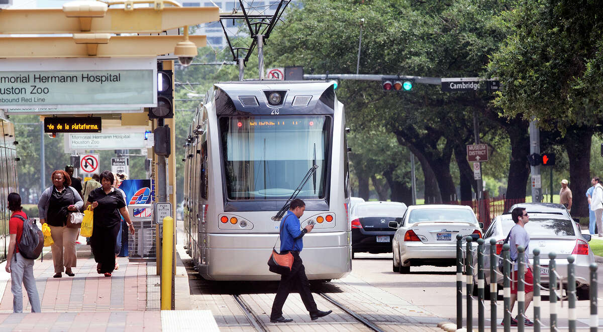 A METRO rail makes its way along the track as a group of pedestrians cross Fannin Street in the Medical Center, Thursday, July 24, 2014, in Houston.