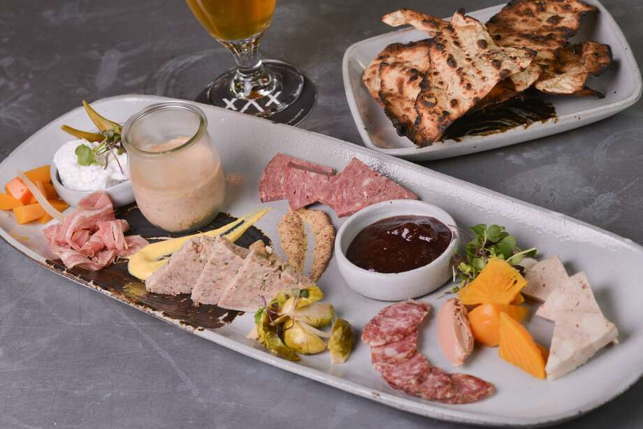 A charcuterie plate from Cured featuring mortadella, chicken liver mousse, jalapeño sauce, apple red wine jam, pickled Brussels sprouts, country style pork pâté, smoked veal wurst, smoked lamb belly, whipped pork butter and beer flatbread. Photo: Robin Jerstad /For The Express-News / San Antonio Express-News