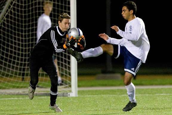 "Summer Creek goalie Craig Myron nearly collides with College Park's Julian Fernandez during a District 16-6A boys soccer game. Coach Paul Kunkel calls Myron ""a good, hardworking kid."""