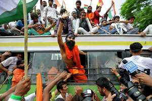 Indian yoga guru Baba Ramdev waves out of the window of a bus after he was detained with his supporters by policemen in New Delhi, India, Monday, Aug. 13, 2012. Waving Indian flags and shouting slogans, the protesters climbed into a row of police buses parked around the sprawling New Delhi fairground that Ramdev and his supporters had occupied for the past four days. (AP Photo/Saurabh Das)