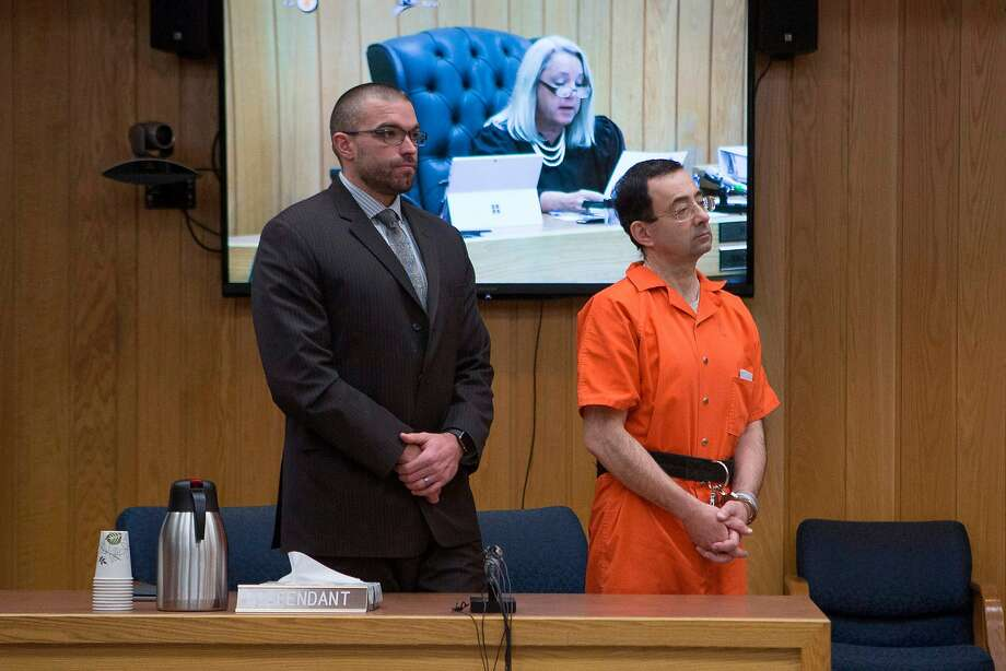 Larry Nassar (right) listens to Judge Janice Cunningham (on screen) at his sentencing in Charlotte, Mich. More than 260 women and girls have reported being molested by Nassar. Photo: RENA LAVERTY, AFP/Getty Images