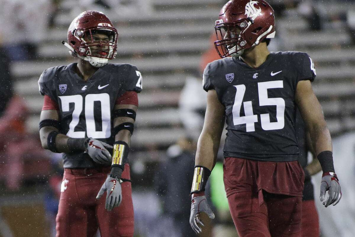 Washington State linebacker Dominick Silvels and defensive lineman Logan Tago stand on the field during the second half of an NCAA college football game against Colorado in Pullman, Wash., Saturday, Oct. 21, 2017.